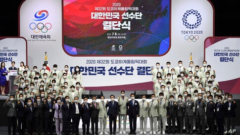 South Korean athletes and staff members pose for a photo during a ceremony to send the South Korean delegation to the Tokyo…