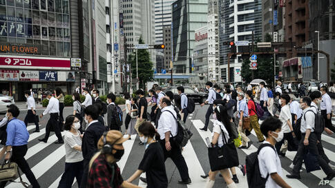 Commuters cross the street during a morning rush hour ahead of the 2020 Summer Olympics, Tuesday, July 13, 2021, in Tokyo. The…
