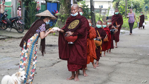 Buddhist monks wearing face mask receive food from devotee as they collect morning alms Thursday, July 15, 2021, in Yangon,…
