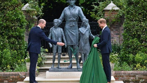 Britain's Prince William, left and Prince Harry unveil a statue they commissioned of their mother Princess Diana,  on what woud…
