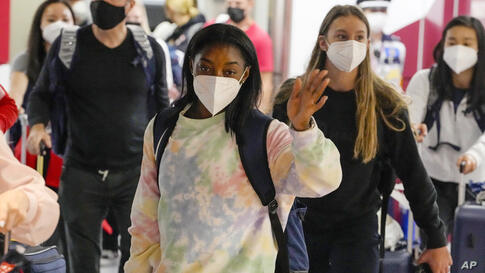Simone Biles, center, and the U.S. Women's Gymnastics team arrive for the Tokyo 2020 Summer Olympic Games at Narita…