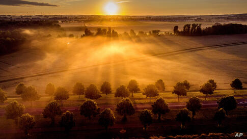 The sun rises over fog covered field on the outskirts of Frankfurt, Germany, early Tuesday, July 6, 2021. (AP Photo/Michael…