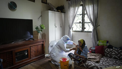 A nurse administers a Pfizer COVID-19 vaccine to an elderly woman in her house in rural Sabab Bernam, central Selangor state,…