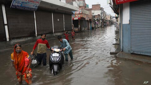 People wade through a water logged street after heavy monsoon showers in New Delhi, India, Monday, July 19, 2021. (AP Photo…