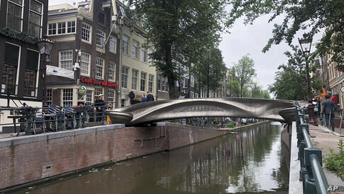 A steel 3D-printed pedestrian bridge spans a canal in the heart of the red light district in Amsterdam, Netherlands, Thursday,…