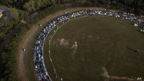 People line up at a drive-thru vaccination center at the Ruben Dumot Autodrome for shots of Pfizer's COVID-19 vaccine in…