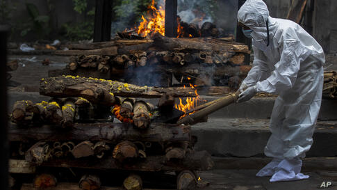 A relative lights the funeral pyre of a COVID-19 victim in Gauhati, India, Friday, July 2, 2021. India on Friday crossed the…