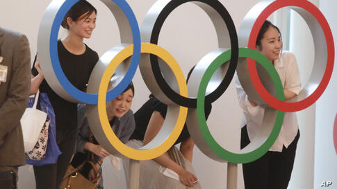 People pose for photo with the Olympics Rings display at Haneda International Airport in Tokyo, Thursday, July 8, 2021. (AP…