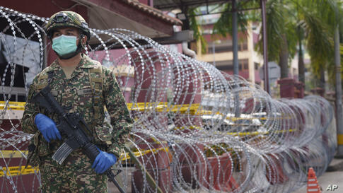 An armed soldier stands guard outside a high density residential area placed under the enhanced movement control order (EMCO)…
