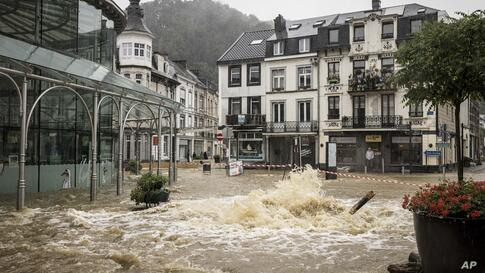 A shopkeeper watches floodwaters run down a main street in the center of Spa, Belgium, Wednesday, July 14, 2021. A code red was…