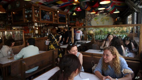 People have fun in a restaurant in Istanbul, Thursday, July 1, 2021. Turkey's government  on Thursday eased restrictions in…