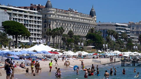 Members of the public take a swim in the sea in front of the Carlton hotel ahead of the 74th international film festival,…
