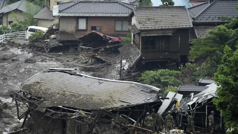 Japan Ground Self-Defense Force members search a mudslide area following heavy rains in Atami, Shizuoka Prefecture, west of…