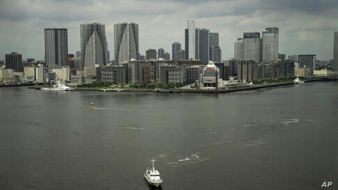 A boat navigates through Tokyo Bay as the athlete's village for the 2020 Summer Olympics and Paralympics is seen in the…
