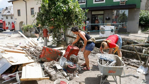 """Residents of the city """"Hallein"""" clean up the flooded houses after the heavy rain in Salzburg, Austria, Monday, July 19, 2021. …"""