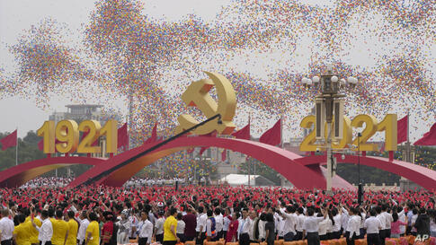 Balloons float over attendees waving Chinese flags during a ceremony at Tiananmen Square to mark the 100th anniversary of the…