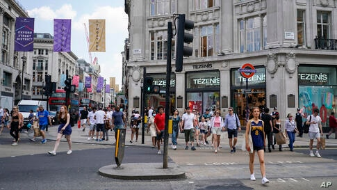 People walk in Oxford Circus, in London, Monday, July 19, 2021. As of Monday, face masks are no longer legally required in…