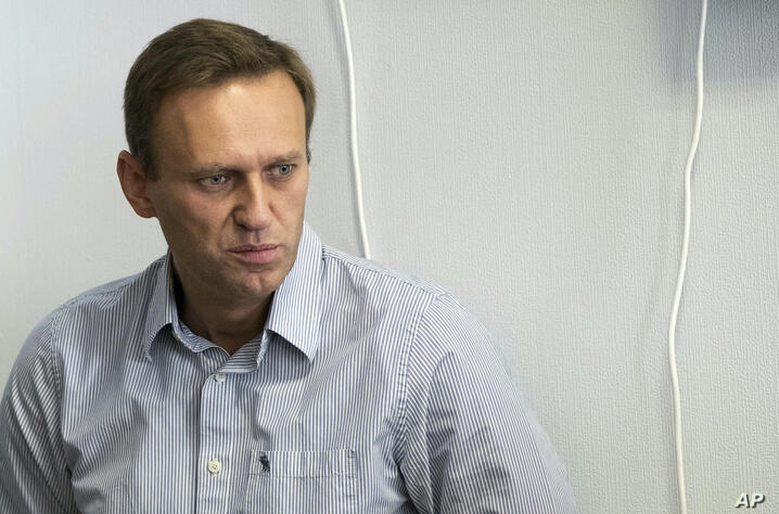 Russian opposition leader Alexei Navalny stands in a corridor during a break in the hearing on his appeal in a court in Moscow,…