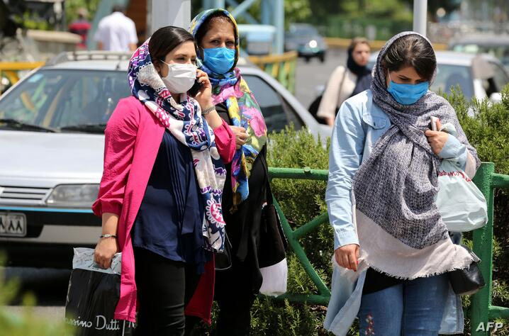 Pedestrians wearing protective masks due to the COVID-19 coronavirus, walk along a street in the Iranian capital Tehran on June…