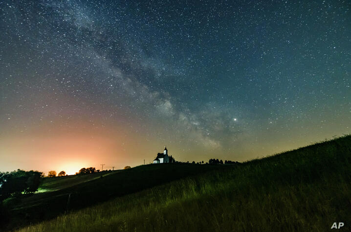 The Milky Way galaxy and the Jupiter, right, are pictured near Gemersky Jablonec, or Gomoralmagy in Hungarian, in southern…