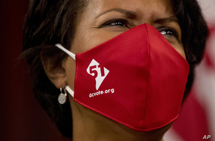 District of Columbia Mayor Muriel Bowser wears a mask with the number 51 over a map of the District of Columbia during a news…