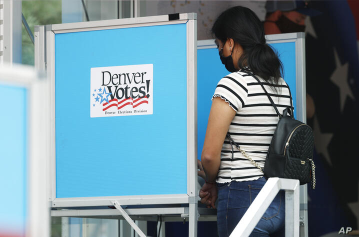 A voter casts her ballot at a mobile location in the Swansea neighborhood, Tuesday, June 30, 2020, in Denver. (AP Photo/David…