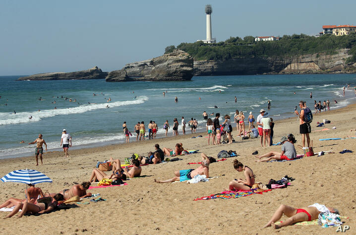People sit on Biarritz beach, southwestern France, Saturday, May 30, 2020. Beaches in France have become partially accessible…