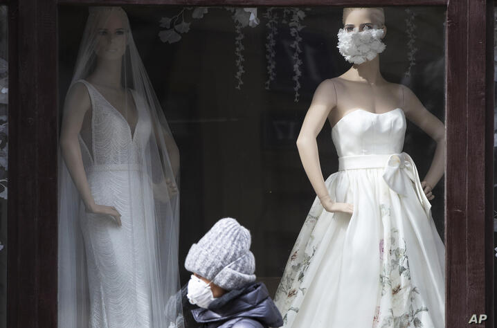 A woman wearing face mask to protect against coronavirus walks past the closed bridal shop with a mannequin decorated with face…