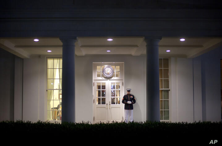 A Marine Honor Guard stands watch at the entrance to the West Wing of the White House Monday night, Sept. 30, 2013.  President…