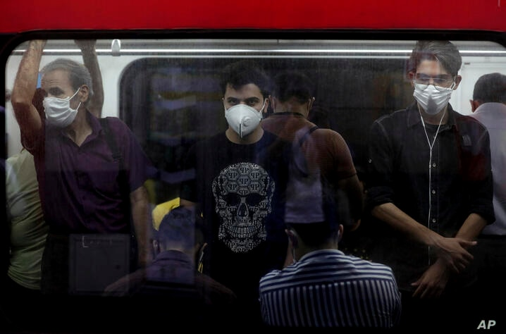 People wearing protective face masks to help prevent the spread of the coronavirus stand inside a train in Tehran, Iran,…