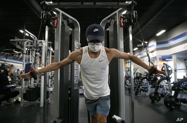 Benji Xiang, 32, wears a mask while working out at a gym in Los Angeles. Friday, June 26, 2020. With the coronavirus surging,…