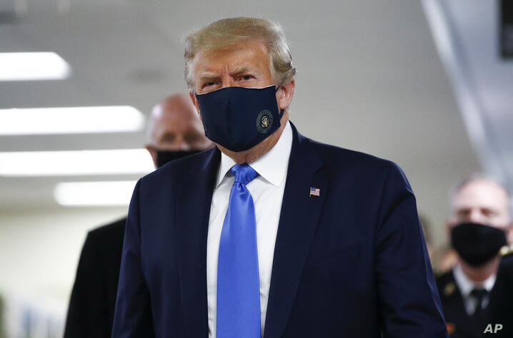 President Donald Trump wears a mask as he walks down the hallway during his visit to Walter Reed National Military Medical…