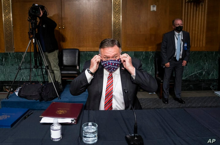 Secretary of State Mike Pompeo removes his mask as he arrives to testify before a Senate Foreign Relations committee hearing on…
