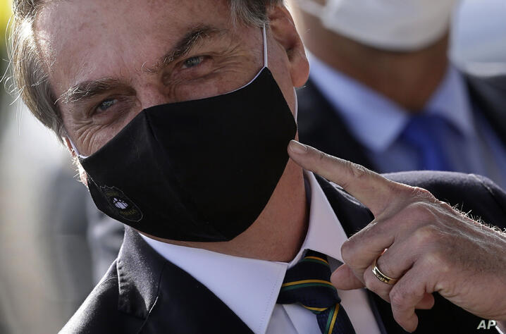 Brazil's President Jair Bolsonaro, wearing a face mask amid the new coronavirus pandemic, speaks to supporters as he leaves his…
