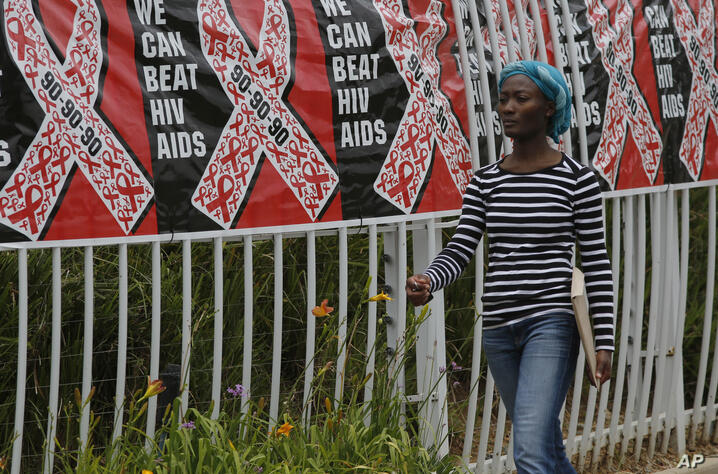 FILE - In this Friday, Dec. 1, 2017 file photo, a woman walks past a World AIDS Day banner in Johannesburg, South Africa. In…