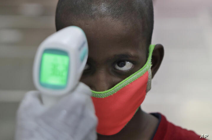 A health worker checks the body temperature of a boy at a medical camp to screen residents for COVID-19 symptoms in Mumbai,…