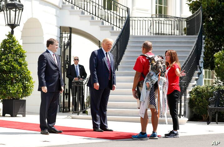 """President Donald Trump greets Terry Sharpe, known as the """"Walking Marine"""" at the White House, Monday, July 27, 2020. Sharpe has…"""