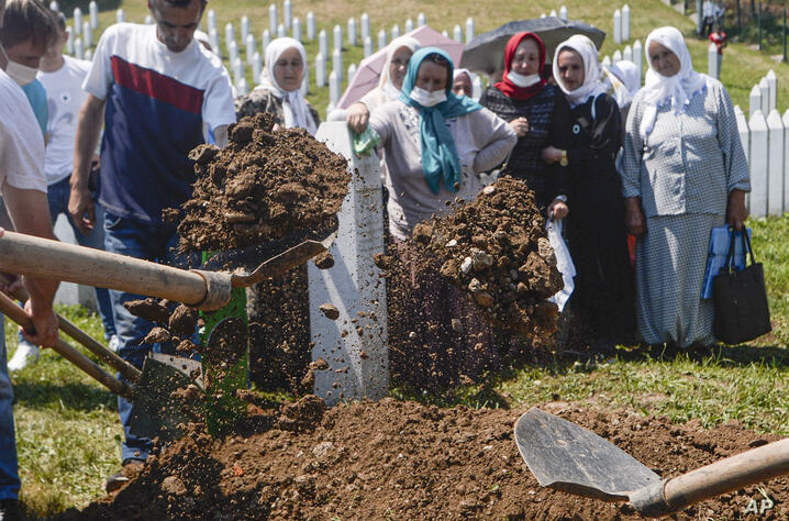 Women watch as one of the massacre victims is buried in Potocari, near Srebrenica, Bosnia, Saturday, July 11, 2020. Mourners…
