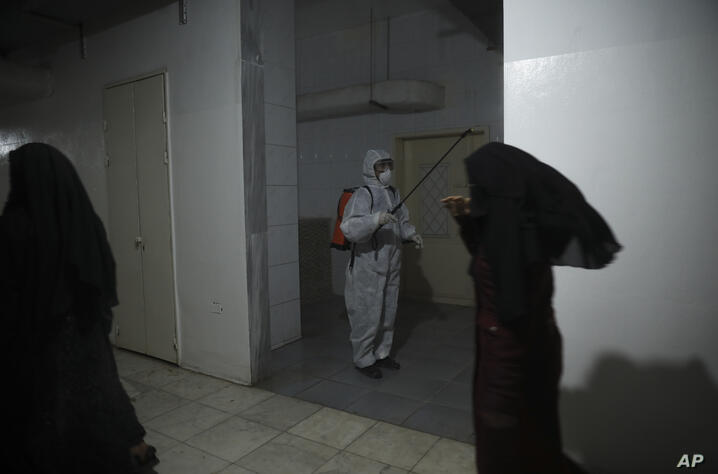 FILE - In this March 19, 2020 file photo, a member of a humanitarian aid agency disinfects inside Ibn Sina Hospital as…