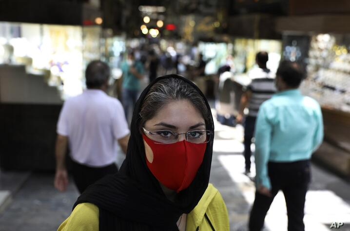 Reyhane Rajaei wearing a protective face mask to help prevent the spread of the coronavirus speaks with The Associated Press at…