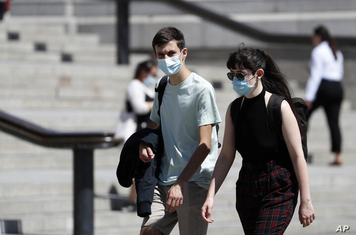 A couple of pedestrian walk through Trafalgar Square waering masks to help combat COVID-19 in London, Thursday, July 30, 2020…