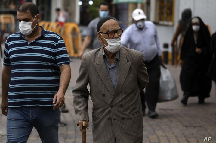 People wearing protective face masks to help prevent the spread of the coronavirus walk on a sidewalk in the city of Zanjan,…