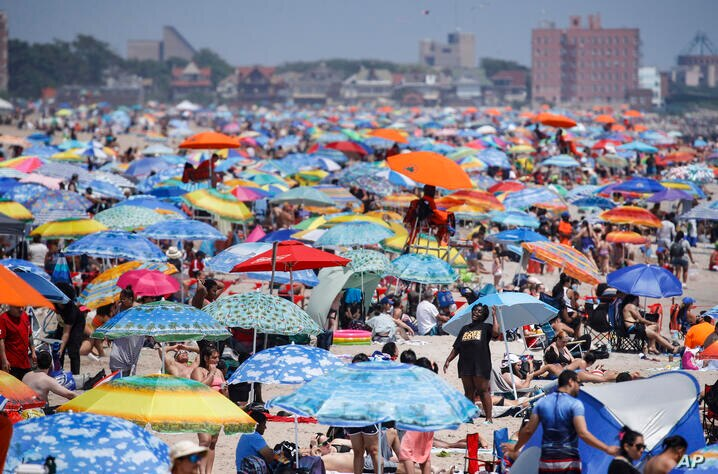Revelers enjoy the beach at Coney Island, Saturday, July 4, 2020, in the Brooklyn borough of New York. (AP Photo/John Minchillo)