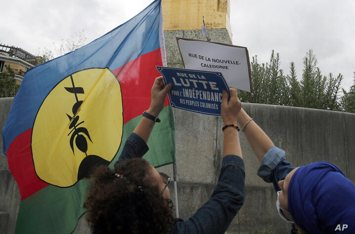 "Anti-racism groups members change streets signs from ""French New Caledonia"" to ""Street of the struggle for the independence of…"
