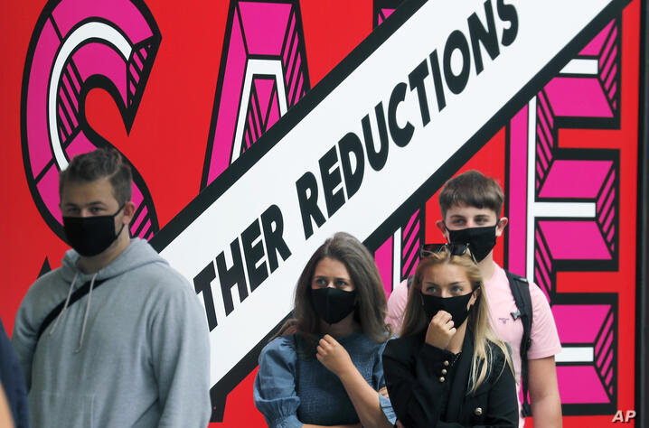 Shoppers wear face masks to protect themselves from COVID-19 as they queue, outside a shop in London, Friday, July 24, 2020…