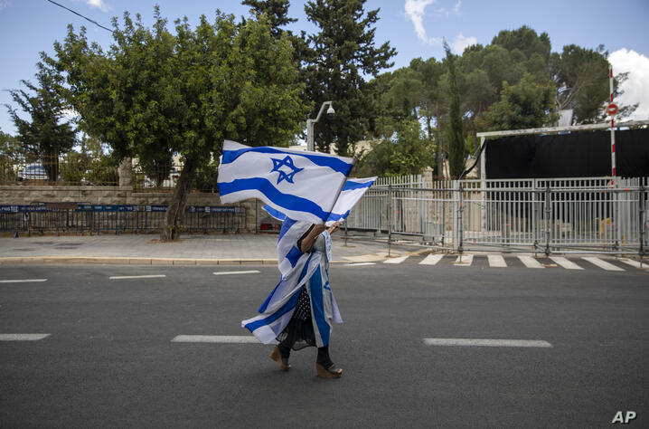 A supporter of Israel's Prime Minister Benjamin Netanyahu waves flags outside his residence in Jerusalem, Sunday, May 24, 2020…