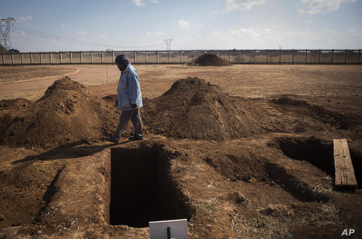 A worker walks past a freshly-dug graves at the Honingnestkrans Cemetery, North of Pretoria, South Africa, Thursday, July 9,…