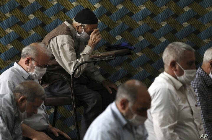 Worshippers wearing protective face masks to help prevent the spread of the coronavirus pray at a mosque in the the city of…
