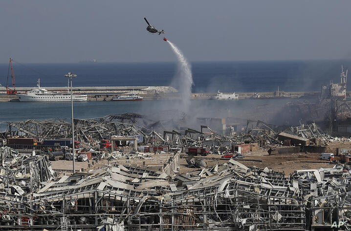 An army helicopter drops water at the scene of Tuesday's massive explosion that hit the seaport of Beirut, Lebanon, Wednesday,…