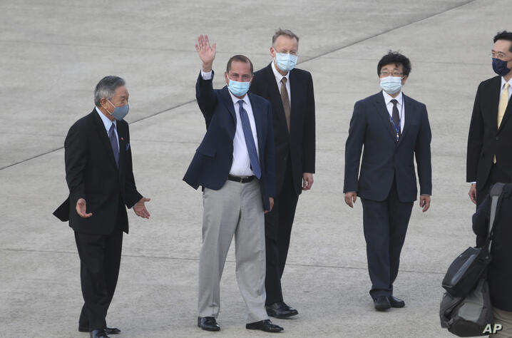 U.S. Health and Human Services Secretary Alex Azar, second left, waves to media as he arrives at Taipei Songshan Airport in…